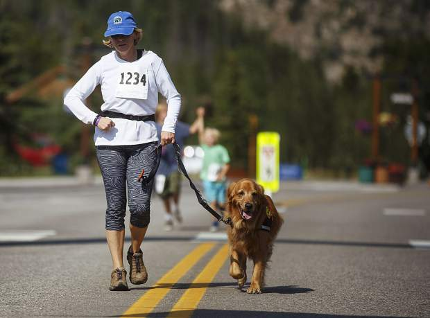 Canine 4K participants jog the last stretch of the race on Frisco's Main Street, Saturday.