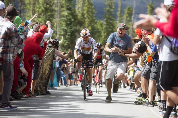 A spectator attempts to stay out of the way of the competing cyclists during the Colorado Classic's Stage 2 race on Boreas Pass Road Friday, Aug. 11 in Breckenridge.