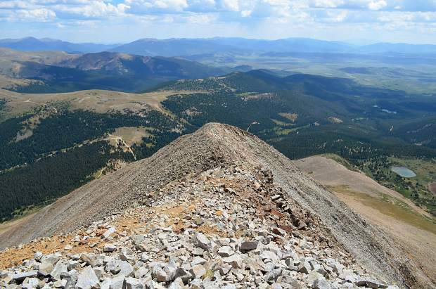 Looking down Guyot's rocky spine towards the ever-so-expansive valley of Park County. From Guyot's summit there are mountain ranges as far as the eye can see.