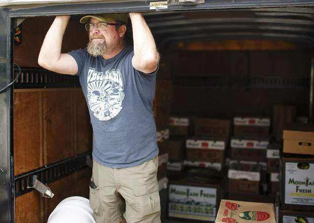 Uncle John's Farm Stand owner Chris Brower takes a break while unloading the trailer full of fresh produce Saturday, Sept. 9, in Frisco.