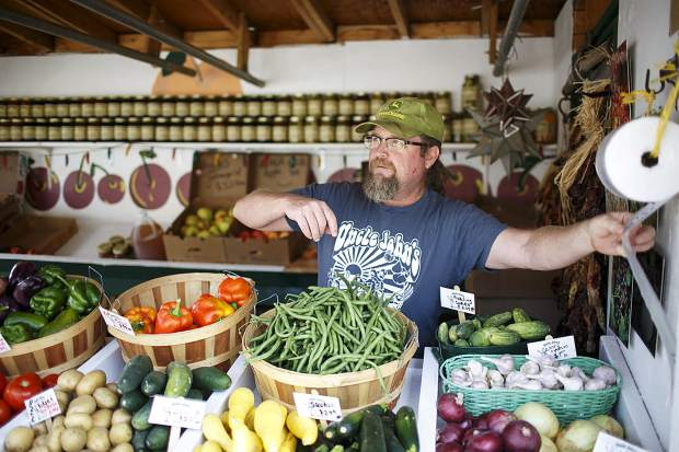 Uncle John's Farm Stand owner Chris Brower serves fresh produce to customers Saturday, Sept. 9, in Frisco.