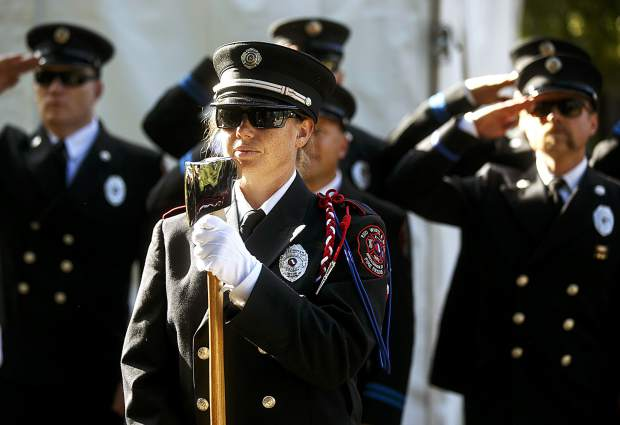 Red, White, and Blue Fire Protection District firefighter Joan Ferris holds the pick head axe during a community remembrance ceremony at the Blue River Plaza Monday, Sept. 11, in Breckenridge.