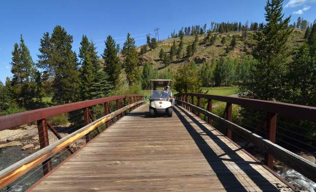 A cart crosses one of several bridges over the Swan River on The River Course at Keystone golf club. The course, opened in 2000, was designed by Dr. Michale Hurdzan and Dana Fry to highlight the hilly terrain along the Swan.