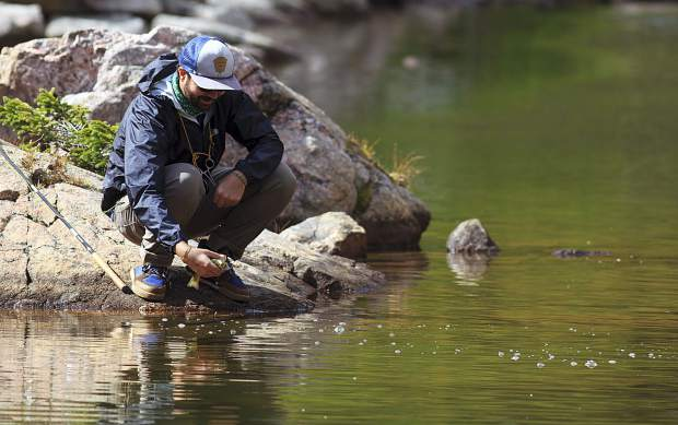 Boulder resident Nick Cote releases fish back into the upper Willow Lake Saturday, Sept. 17, near Silverthorne.