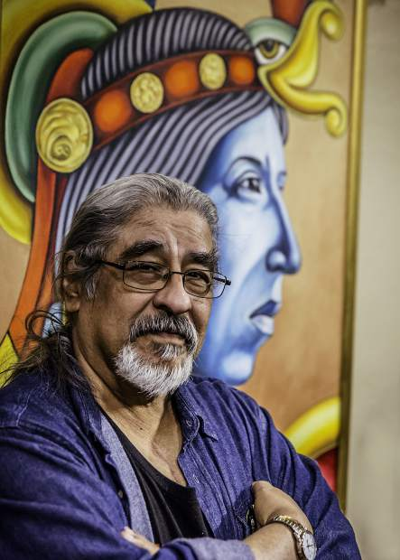 Artist Stevon Lucero stands with one of his paintings, which re-visions images of Pre-Columbian Mexico into new vibrant paintings of power and depth.