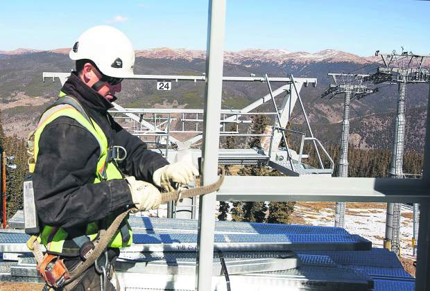 Keystone construction worker Eric Mills adjusts his harness and rope line to prevent from falling while working from the top terminal of Montezuma Express Lift Friday, Oct. 13, on Dercum Mountain at Keystone Ski Resort.