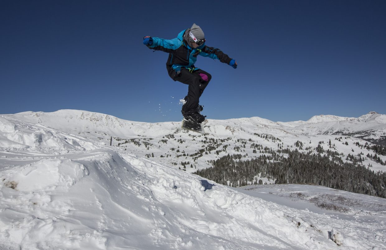 A snowboarder goes airborne off a jump Tuesday, Oct. 3, at Loveland Pass.