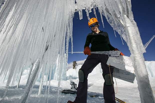 Helan Dubas harvests icicles during the construction for the ice castle Wednesday, Dec. 20, at the site in Dillon Town Park.
