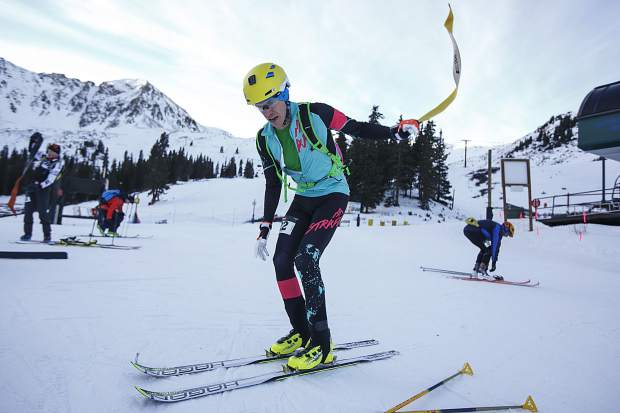 Ski mountaineering competitor Chris Carr transitions to downhill mode while taking off the skins attached to the skis during the
