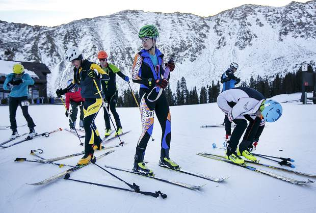 Ski mountaineering competitors transition to downhill skiing mode during the