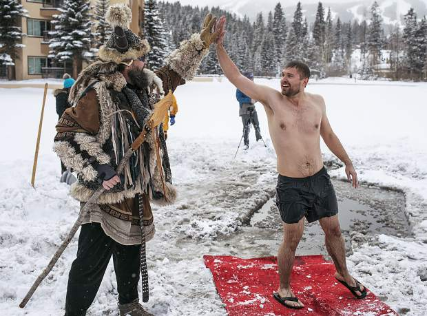 Robert Prus, of Tampa, Fla., high fives Ullr following a dip in the Maggie Pond for the Ullr Ice Plunge Friday, Jan. 12, in Breckenridge.