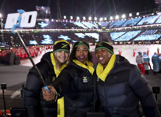 American-born Jazmine Fenlator-Victorian, a former Team USA bobsledder, holds up a selfie stick during the opening ceremony of the 2018 Winter Olympics in Pyeongchang, South Korea on Friday, Feb. 9.