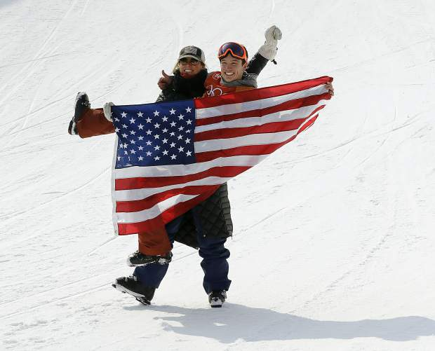 CORRECTS TO SILVER MEDAL NOT GOLD - Silver medal winner Alex Ferreira, of the United States, is carried by his coach, Elana Chase, after the men's halfpipe final at Phoenix Snow Park at the 2018 Winter Olympics in Pyeongchang, South Korea, Thursday, Feb. 22, 2018. (AP Photo/Lee Jin-man)