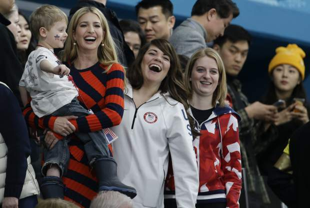 Ivanka Trump, daughter of U.S. President Donald Trump, left, holds a child beside United States' curler Becca Hamilton, center, as they watch the men's final curling match between United States and Sweden at the 2018 Winter Olympics in Gangneung, South Korea, Saturday, Feb. 24, 2018. (AP Photo/Natacha Pisarenko)