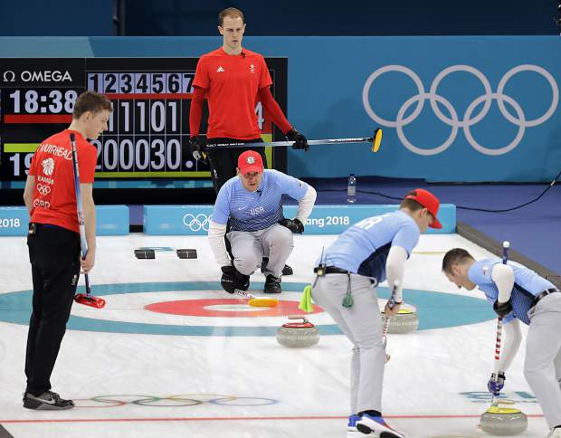 Britain's skip Kyle Smith, second from left, stands behind United States' skip John Shuster during their men's curling match at the 2018 Winter Olympics in Gangneung, South Korea, Wednesday.