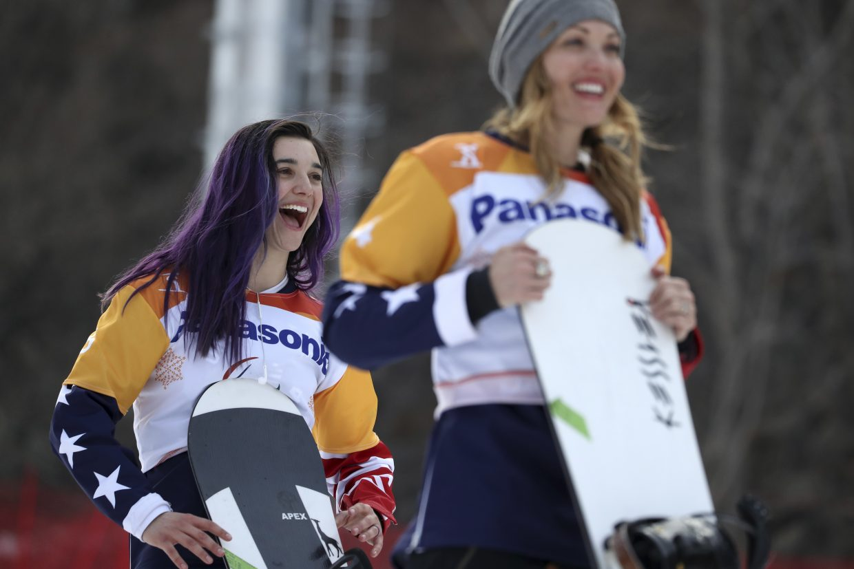 Winners of the Women's Snowboard Cross SB-LL1 event from left gold medalist Brenna Huckaby of United States and silver medalist Amy Purdy of United States react during a ceremony at the 2018 Winter Paralympics at the Jeongseon Alpine Centre in South Korea, Monday, March 12, 2018.