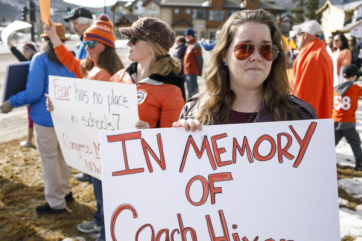 South Florida area high school graduate and current Breckenridge resident Becky Van Horn, 24, holds the sign remembering her late Coach Chris Hixon, who was killed in the shooting shooting in Parkland, Florida, during a