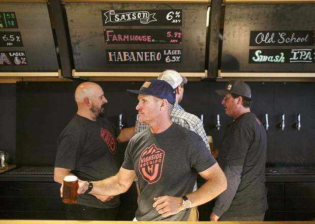 Bartenders serve beer at High Side Brewery during the opening day Friday, May 18, on Main Street in Frisco.