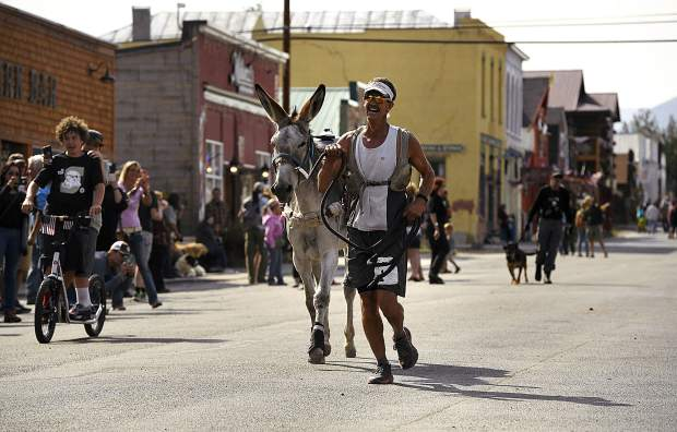 Kirt Courkamp, of Pine, right, smiles with joy as he and his donkey Mary Margaret win the 29-mile race at the 70th annual World Championship Pack Burro Race in Fairplay with a time of 6 hours, 6 minutes and 38 seconds. Courkamp and Margaret won the race for the third year in a row. Each runner must lead his or her donkey with a 15 foot lead rope and the donkey must carry 33 pounds in its pack. The runner is allowed to push, pull, drag or carry the burro but is not allowed to ride it.