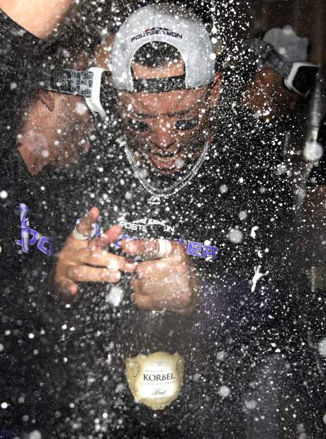 The Colorado Rockies' Carlos Gonzalez celebrates with teammates in the club house after defeating the Chicago Cubs 2-1 in the National League wild-card playoff baseball game early Wednesday in Chicago.