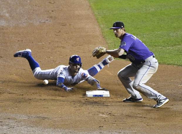 Chicago Cubs' Javier Baez, left, slides into second base safely as he hit a one-run double as Colorado Rockies second baseman DJ LeMahieu (9) makes a late tag during the eighth inning of the National League wild-card playoff baseball game, Tuesday, Oct. 2, 2018, in Chicago.