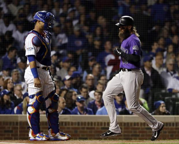 Colorado Rockies' Charlie Blackmon, right, scores on a sacrifice fly as Chicago Cubs catcher Willson Contreras looks to the field during the first inning of the National League wild-card playoff baseball game Tuesday, Oct. 2, 2018, in Chicago.