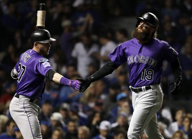 Colorado Rockies' Charlie Blackmon, right, celebrates with Trevor Story after scoring on a sacrifice fly by Nolan Arenado during the first inning of the National League wild-card playoff baseball game against the Chicago Cubs, Tuesday, Oct. 2, 2018, in Chicago.