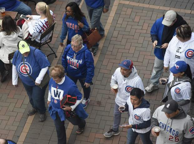 Fans head to the ballpark before the National League wild-card playoff baseball game between the Chicago Cubs and the Colorado Rockies, Tuesday, Oct. 2, 2018, in Chicago.
