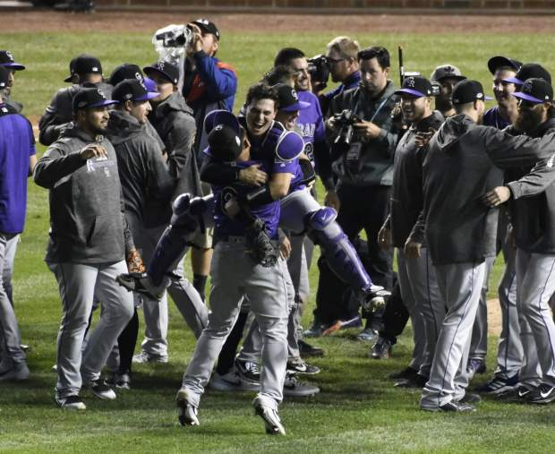 The Colorado Rockies celebrate their win against the Chicago Cubs in the National League wild-card playoff baseball game on Wednesday in Chicago. The Rockies won 2-1.