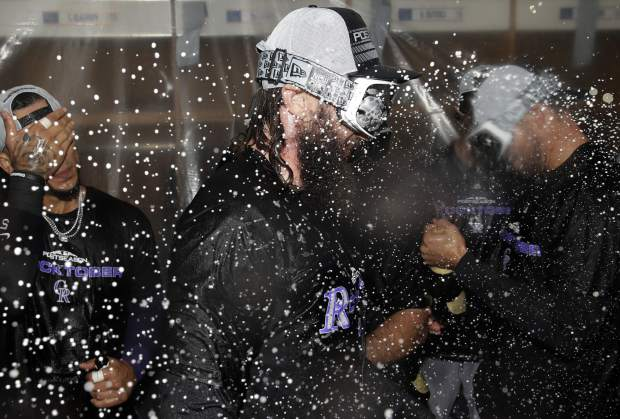 The Colorado Rockies' Charlie Blackmon celebrates with teammates in the clubhouse after defeating the Chicago Cubs 2-1 in the National League wild-card playoff baseball game early Wednesday in Chicago.