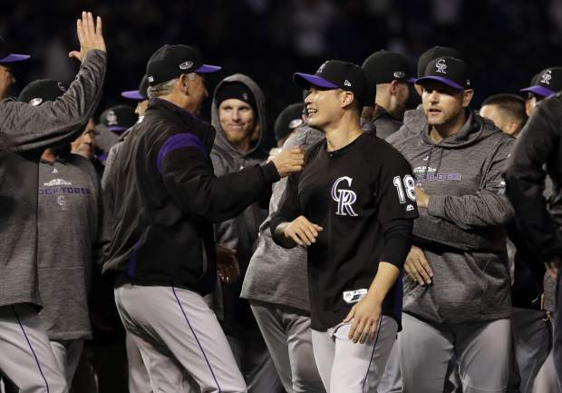 Colorado Rockies relief pitcher Seunghwan Oh, second from right, of South Korea, celebrates with manager Bud Black after the Rockies defeated the Chicago Cubs 2-1 in the National League wild-card playoff baseball game Tuesday, Oct. 2, 2018, in Chicago.