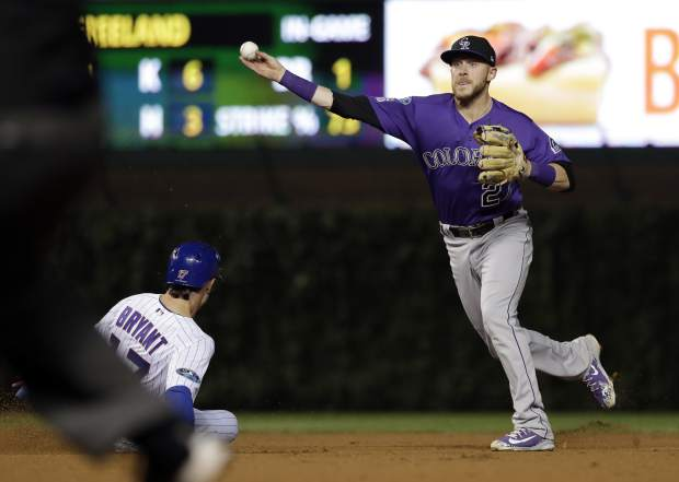 Colorado Rockies shortstop Trevor Story, right, throws out Chicago Cubs' Anthony Rizzo at first after forcing out Kris Bryant at second during the sixth inning of the National League wild-card playoff baseball game Tuesday, Oct. 2, 2018, in Chicago.