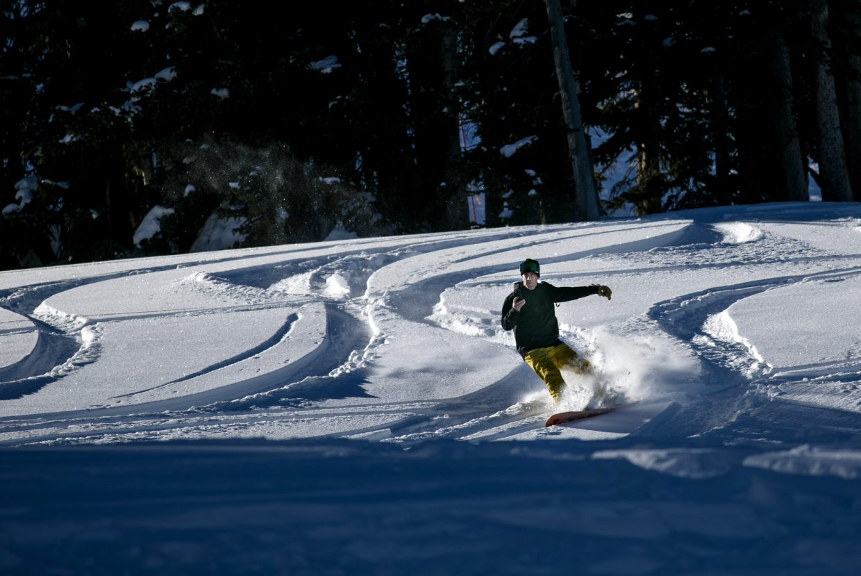 A snowboarder with a cellphone make turns on the opening day of 2018-2019 season Friday, Nov. 16, at Copper Mountain.