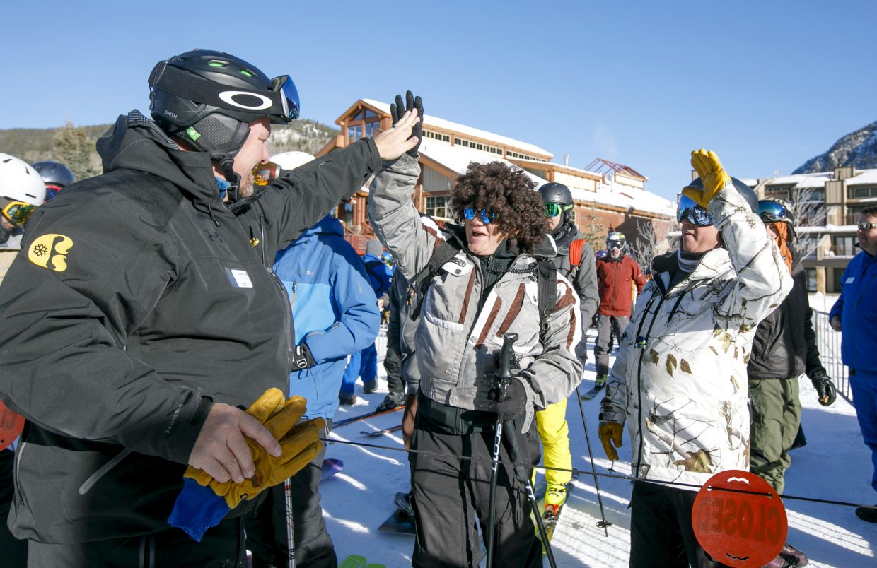 Copper Ski Resort Chief Operations Officer Jesse True  high fives first chairlift riders of the 2018-2019 ski season Friday, Nov. 16, in Copper Mountain's East Village.