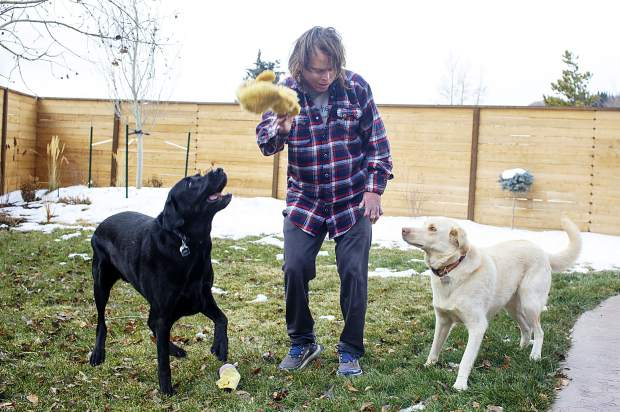 Dave Repsher plays with his dogs, Tucker, left, and Turq, in the backyard Saturday, Nov. 17, at home in Silverthorne.
