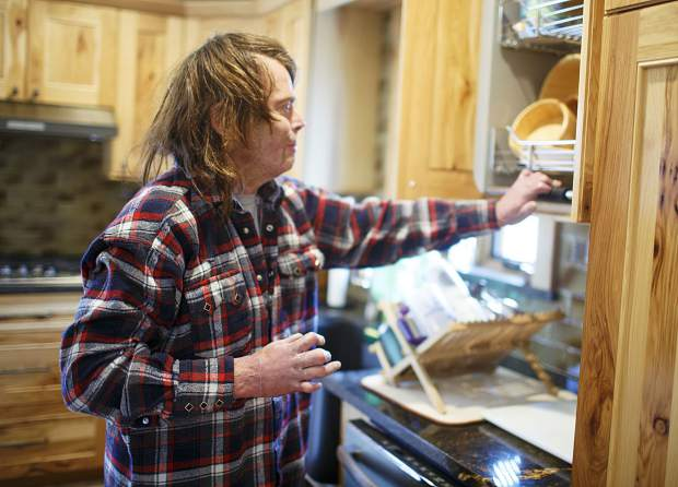Dave Repsher uses the handicap friendly roll down shelves from the kitchen cupboards Saturday, Nov. 17, at home in Silverthorne. Many people helped Dave and Amanda Repsher remodel the couple's home, making it more comfortable for Dave Repsher, who was badly burned in a July 2015 helicopter wreck.