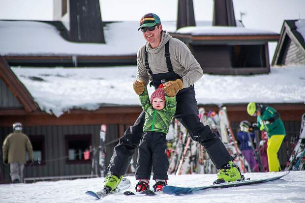 Phillip Supino skis with his son Charles, 2, for his first day in his life on skis on Aspen Mountain for opening day Saturday.