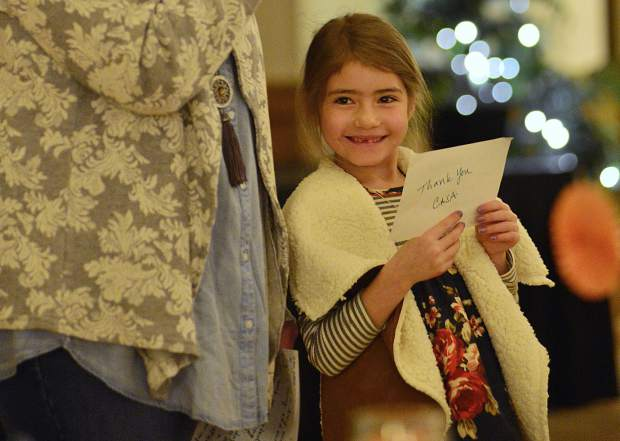 """Six-year-old Lily smiles while holding up a note card that says """"Thank You CASA"""" on the back of it as her adoptive mom, Amy Geppi, talks about how a court-appointed special advocated helped with the adoption Wednesday during CASA of the Continental Divide's celebration dinner at the Silverthorne Pavilion."""