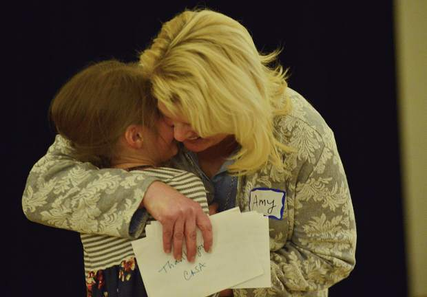 Amy Geppi gives her adopted 6-year-old daughter, Lily, a hug after Lily thanked CASA of the Continental Divide during the nonprofit's celebration dinner Wednesday night at the Silverthorne Pavilion.