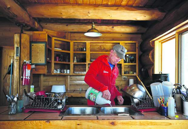 Summit Huts Association hutmaster Steve Huyler cleans the sinks and the pipes at Francie's Cabin on Tuesday, Feb. 5, near Blue River.