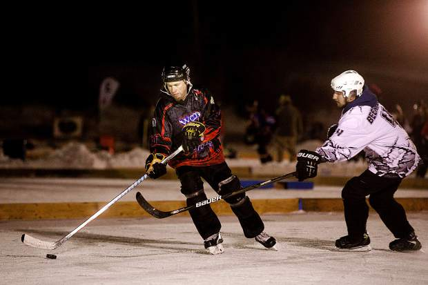 Three-player hockey teams teams attempt to gain control of the puck during the Pabst Colorado Pond Hockey tournament Friday night, Feb. 15, at North Pond Park in Silverthorne.