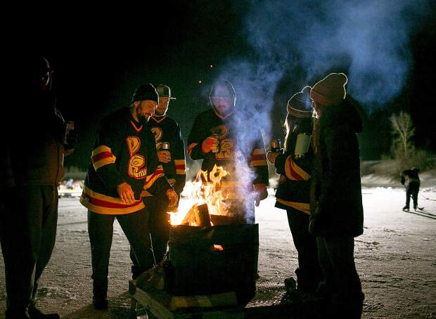 Spectators and thousands of hockey stay warm with fire pits at the North Pond Park during in the Pabst Colorado Pond Hockey tournament Friday night, Feb. 15, in Silverthorne.