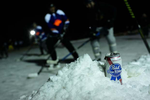 A nearly full PBR can stays cold as spectators and thousands of hockey players gather at North Pond Park to participate in the Pabst Colorado Pond Hockey tournament Friday night, Feb. 15, in Silverthorne.