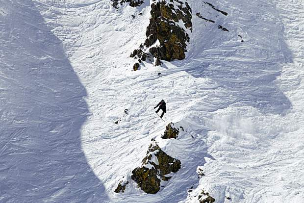 A snowboarder holds a grab after launching off a natural cliff jump within the Six Senses terrain at Breckenridge Ski Resort's Peak 6 during Saturday's Helly Hansen Big Mountain Challenge.