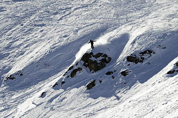 A skier launches off of a natural cliff jump within the Six Senses terrain at Breckenridge Ski Resort's Peak 6 during Saturday's Helly Hansen Big Mountain Challenge.
