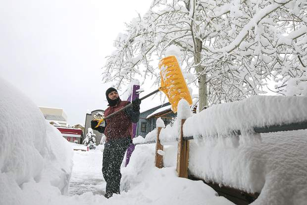 Ellis Ubeda shovels snow off sidewalks along Main Street Thursday, March 7, in Frisco.
