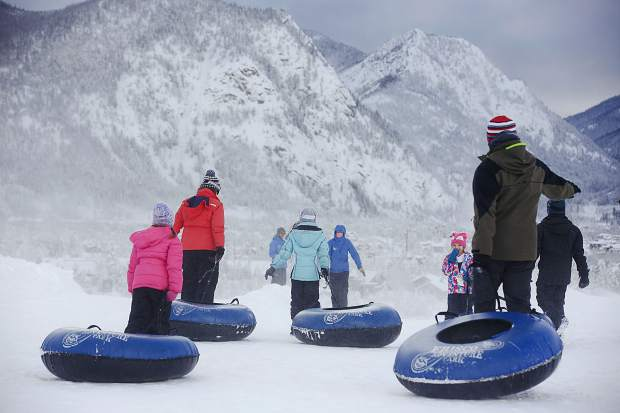 People drag their snow tubes for downhill sledding at the Frisco Adventure Park Thursday, March 7, in Frisco.