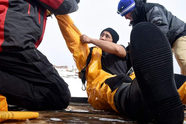 Jesus Munoz, a project manager at A Kinder Carpet in Silverthorne, gets help putting on a Mustang Survival Ice Commander suit. The bright-yellow onesie keeps you warm for hours in frigid temperatures, according to Summit County Sheriff's Office personnel, who were on hand Saturday morning for the placement of the ice device. The device is the centerpiece of an annual fundraiser for the Rotary Club of Summit County.