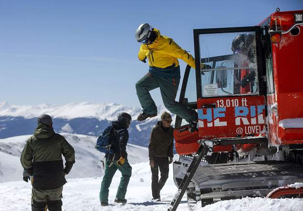A skier jumps off the Ridge Cat snowcat machine, a Piston Bully 600, on Loveland Ski Area Friday, March 15, for high alpine skiing.