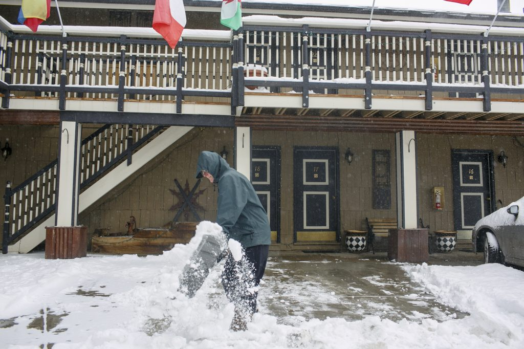 Frisco Lodge employee shovels snow off their parking lot Friday, March 1, along Main Street in Frisco.